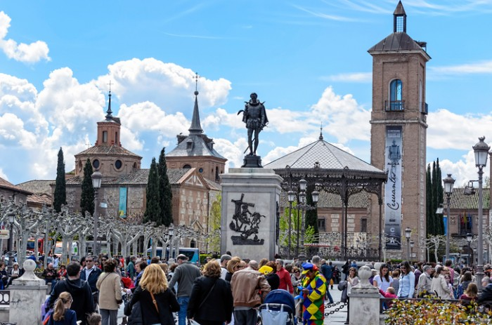 Alcala de Henares, Spain - April 23, 2016: Unknown people are walking by Cervantes's square, during 4th centenary of Miguel de Cervantes's death, in Alcala de Henares, on April 23th 2016. Today, many cultural activities around the writer of  -Don Quixote de la Mancha- are being celebrated in his hometown. Monument of his iron sculpture.
