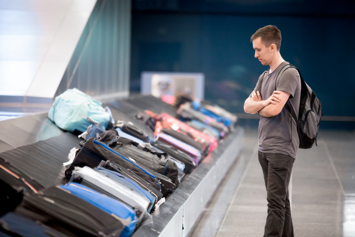 Young handsome man passenger in his 20s with carry-on backpack waiting at conveyor belt to pick his luggage in arrivals lounge of airport terminal building