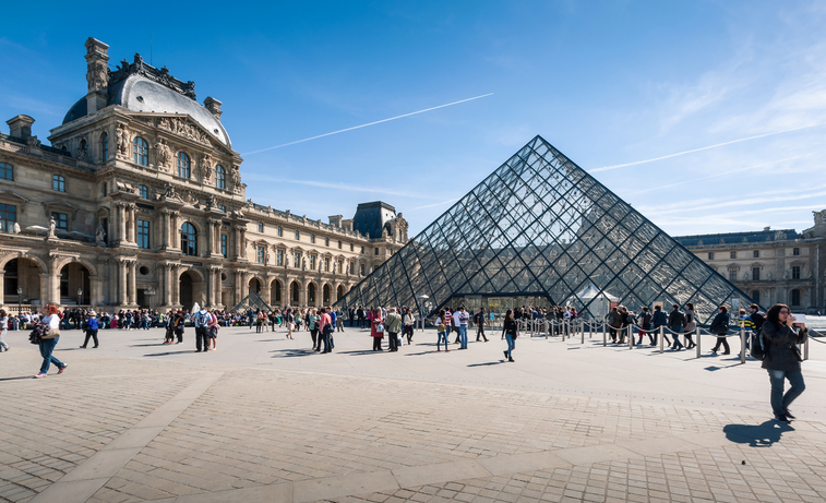 Paris, France - April 14, 2013: Tourists in the Louvre's central courtyards with the Louvre pyramid and palace. The Louvre is the world's most visited museum.