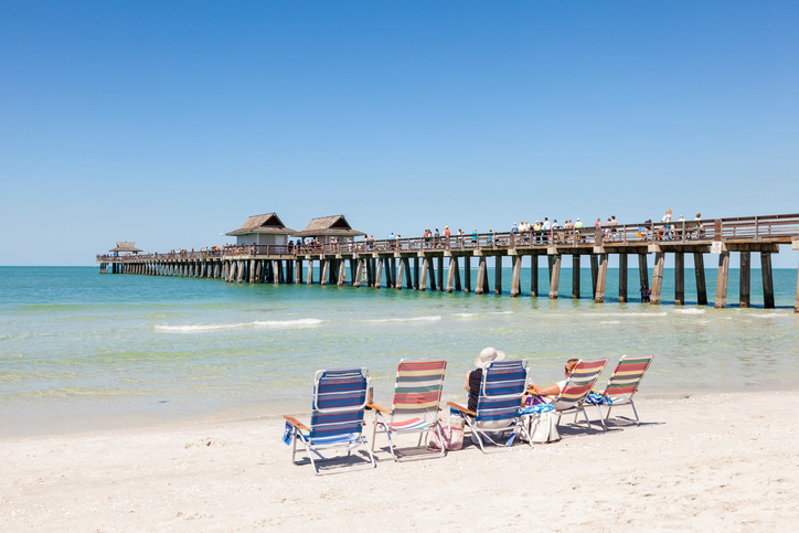 Naples, Fl, USA - March 18, 2017: People enjoying the beautiful white sand beach at the gulf of mexico coast in Naples. Florida, United States