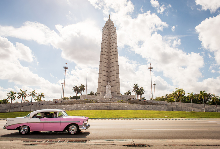 Havana, Cuba - January 21, 2017: A pink vintage car passing the Revolution square in Havana. In the background the José Marti memorial, the highest building of Havana.