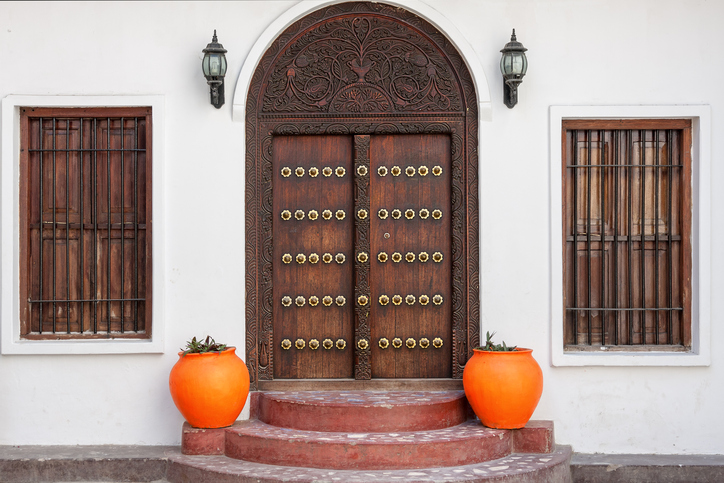 traditional zanzibar wooden door and doorway ornately carved and decorated with pots