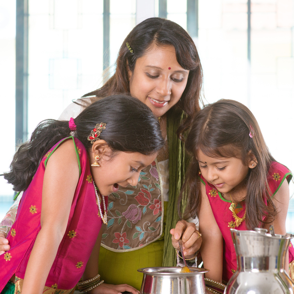 Asian family cooking food together in kitchen. Indian mother and children preparing meal at home. Traditional India people with sari clothing.
