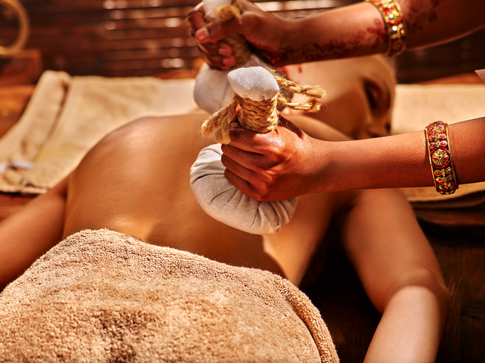 Woman having ayurvedic massage with back pouch of rice. Close up of exotic India massage.