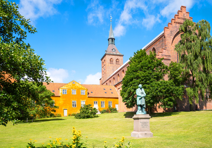 Odense, the gothic St. Canute's Cathedral with the Hans Christian Andersen monument in the foreground