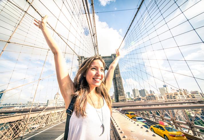Attractive mixed race woman on Brooklyn Bridge - Portrait of pretty girl sightseeing New York