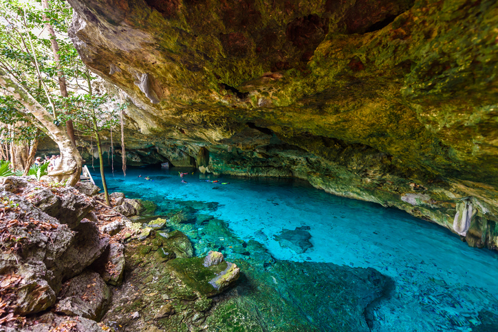 Cenote Dos Ojos in Quintana Roo, Mexico. People swimming and snorkeling in clear blue water. This cenote is located close to Tulum in Yucatan peninsula, Mexico.