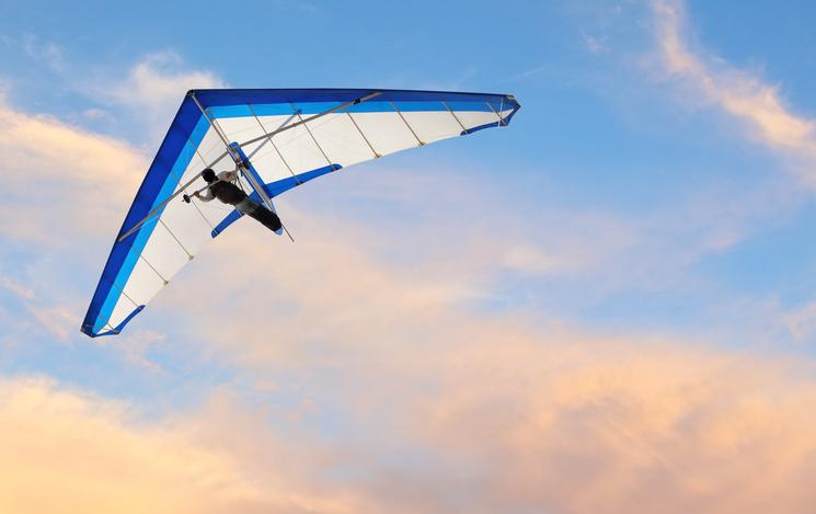 Hang glider fling over the ocean at sunset