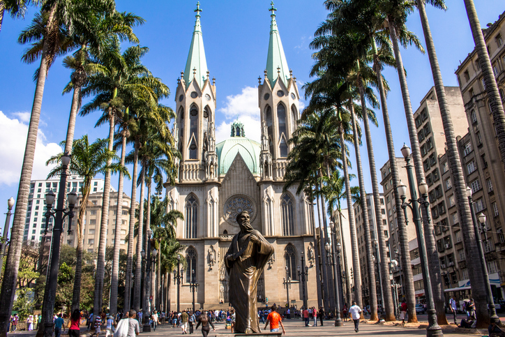 Sao Paulo, Brazil, August 19, 2015. People walking in Se square and facade of Se Metropolitan Cathedral in Sao Paulo, Brazil. Se Cathedral was constructed in 1913 in Neo Gothic Style.