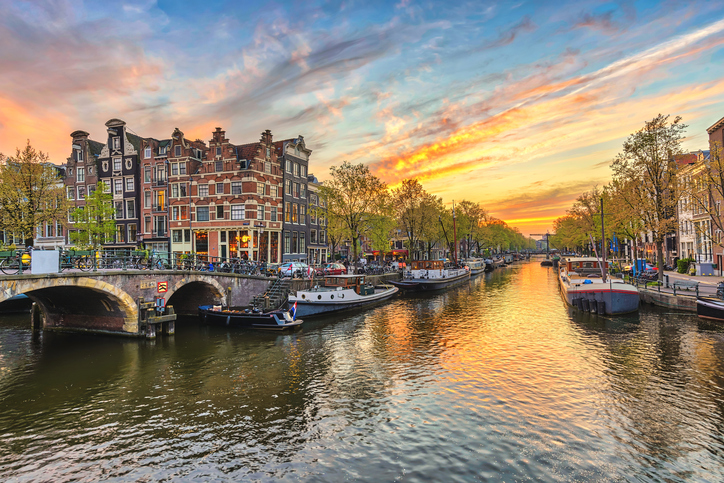 Amsterdam sunset city skyline at canal waterfront, Amsterdam, Netherlands