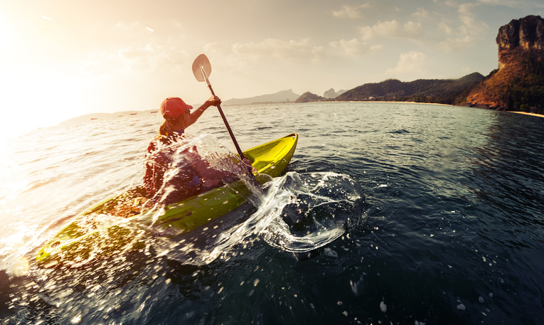 Lady paddling the sea kayak with lots of splashes