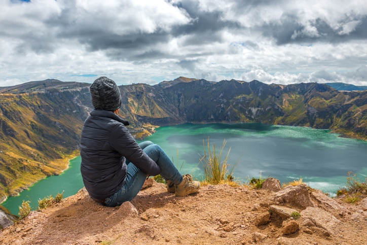Young female backpacker/tourist watching over the Volcanic Quilotoa Crater lake in a moment of contemplation during the Quilotoa Loop hiking Pole. The Quilotoa Crater Lake is located near the city of Latacunga, south of Quito, Ecuador.