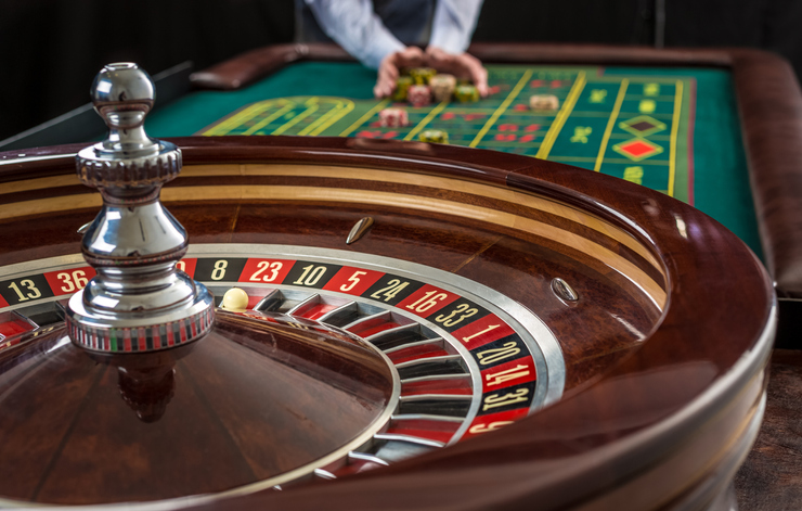 Roulette and piles of gambling chips on a green table in casino.  Man hand over casino chips  - bet.