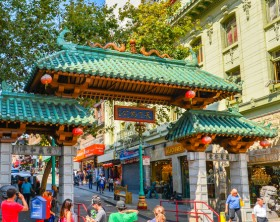 San Francisco, CA - Aug. 15, 2015: Tourists under Dragon Gate, the landmark gateway arch marking the entrance to the city's iconic Chinatown neighborhood.