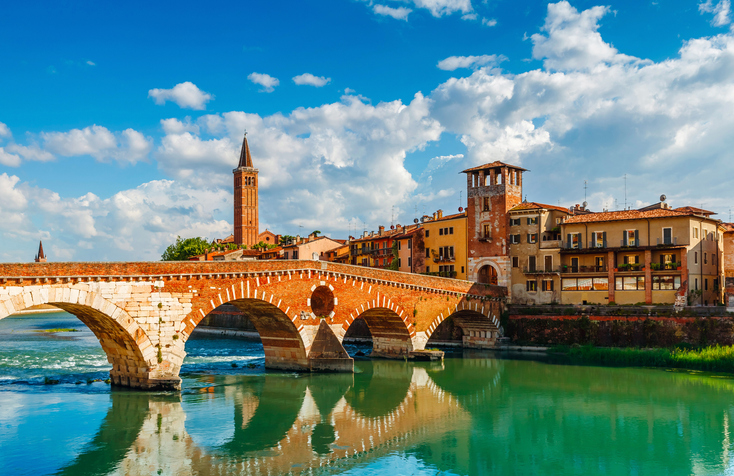 Bridge Ponte Pietra in Verona on Adige river. Veneto region. Italy. Sunny summer day panorama and blue sky with clouds. Ancient european terracotta color houses