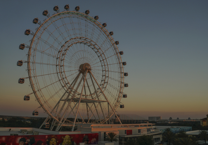 Orlando, FL, USA - March 24, 2018: The Orlando Eye on I Drive, illuminated as the sunset paints the sky orange and yellow.  The Orlando Eye is one of the newest attractions in Orlando and the largest observation wheel on the East Coast of the USA.