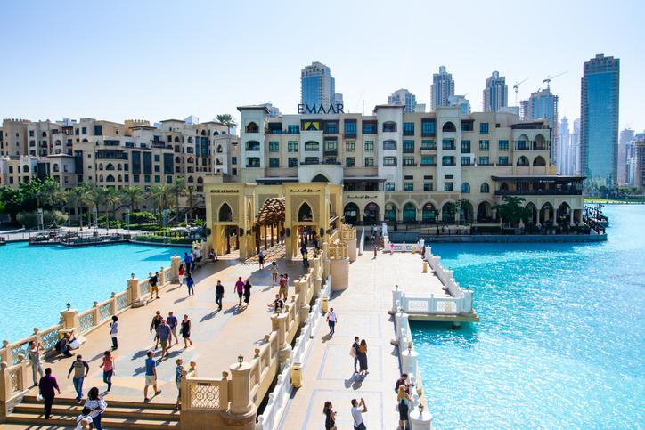DUBAI, UNITED ARAB EMIRATES - OCTOBER 13, 2017: Dubai mall fountain pool with many people walking to see Burj Khalifa tower on a sunny day