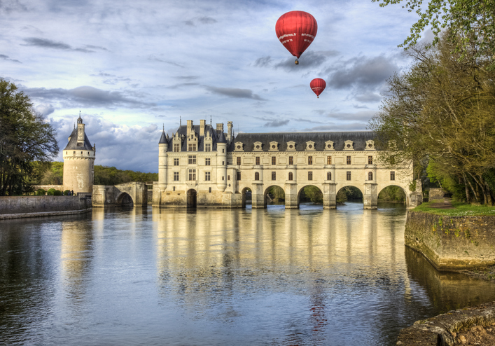 Chenonceaux, France- April 6, 2014: Two red hot air balloons fly above the Chenonceau Castle spanning the river Cher in the Loire Valley ,France.