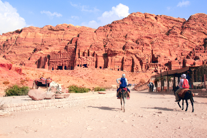 Tourists ride on donkeys in Petra (Red Rose City), Jordan. UNESCO world heritage site