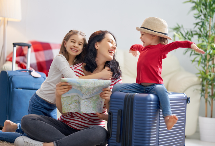 Go on an adventure! Happy family preparing for the journey. Mom and daughters are packing suitcases for the trip.