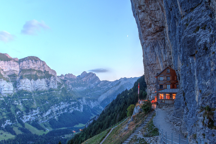 After sunset view of the magical Aescher Cliff (Appenzell Canton, Switzerland) and the moutain restaurant catering to hikers. A crescent moon is visible above the cabin.
