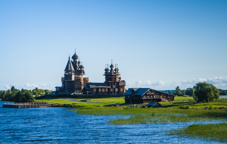 view of Kizhi Island, the historic site of churches, bell tower, a large  historic log wood house on the marshy banks of island which is a UNESCO World Heritage Site