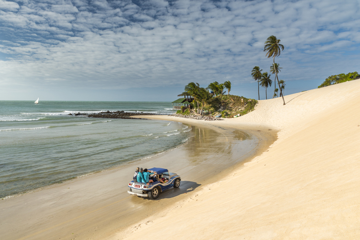 Natal, Rio Grande do Norte, Brazil. 01st September 2017. One buggy (bugre) driving offroad near the sea water at the beach of Genipabu (also known as Jenipabu). Local popular trourist attraction, riding sand dunes on a car is fun.