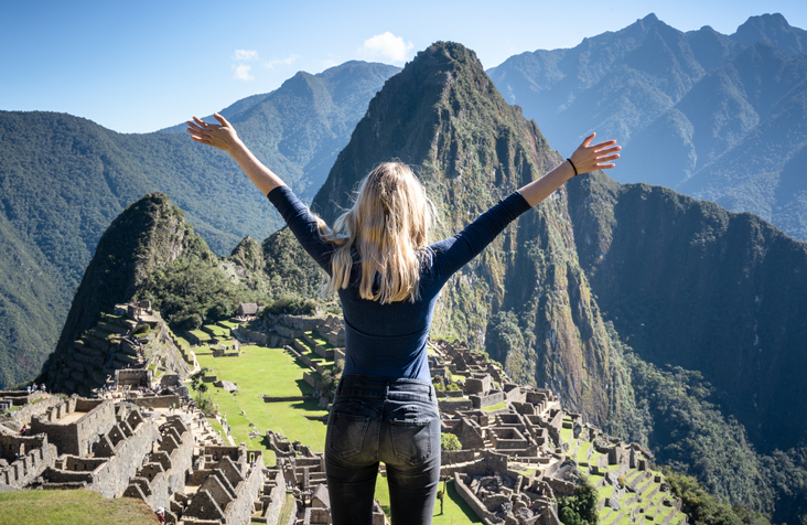 A back view of a blonde young woman, hands in the air, happy to be at Machu Picchu.