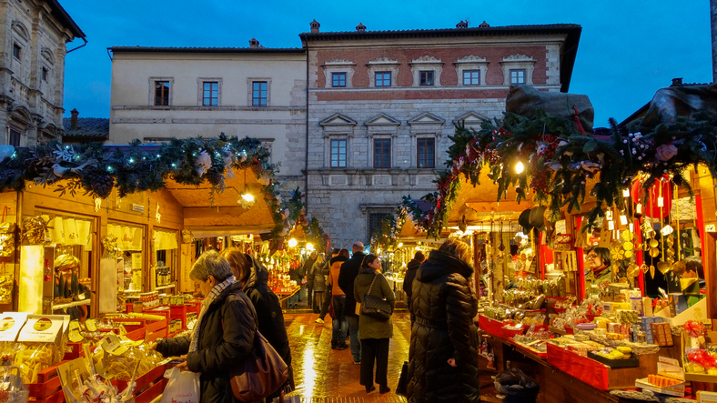 Montepulciano, Italy - November 17, 2019: Montepulciano at Christmas is transformed into a Christmas market (free admission) with over sixty wooden houses where you'll find handicrafts, delicatessen products, decorations and gifts. Inside the Castle of Montepulciano, instead, children can enjoy the Christmas village set up just for them. In this photo there are many happy people making shopping at the christmas market in the main square of Montepulciano medieval town, Tuscany, Italy