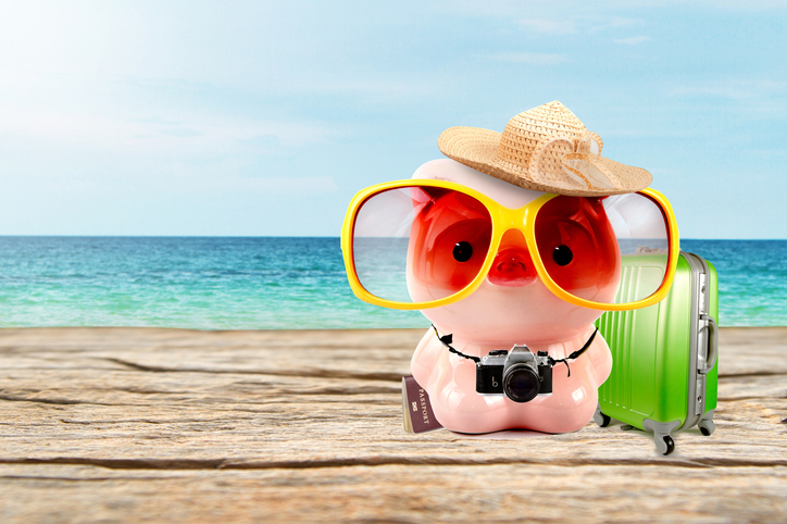 Piggy bank with travel costume and baggage at beautiful blue sky and sea beach.