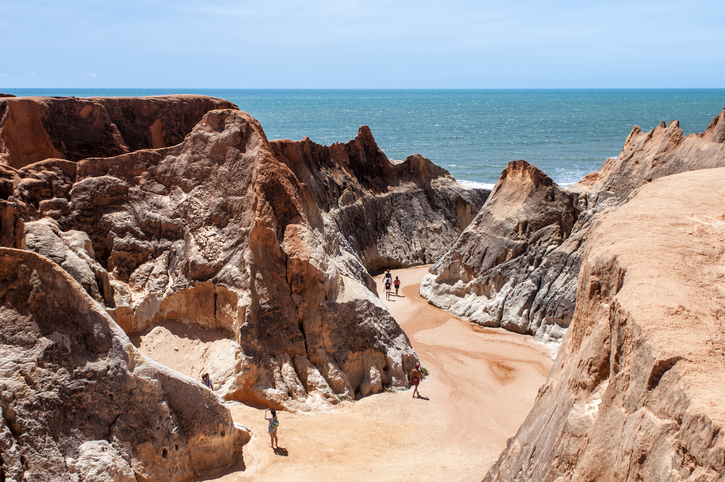 Morro Branco, Ceara State, Brazil - July 27, 2013: Tourists on the rocky beach, near Fortaleza city, in the north-east of Brazil