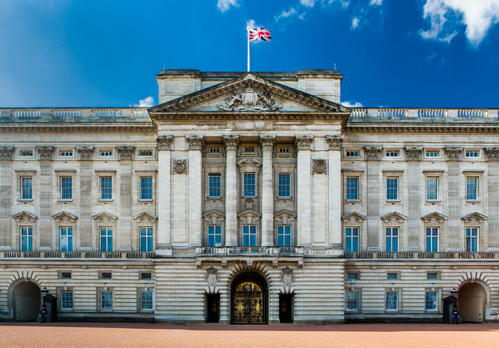 The facade of Buckingham Palace with the Union Flag flying against a clear blue sky.