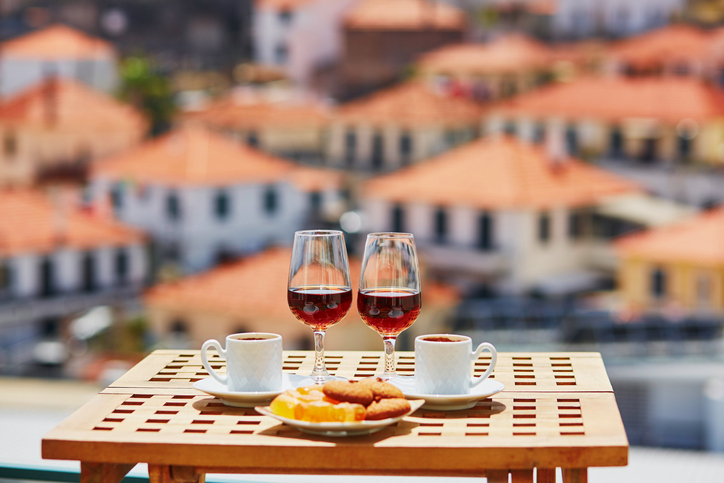 Two glasses of Madeira wine, two cups of fresh espresso coffee and traditional Portuguese sweets in cafe with view to Funchal town, Madeira, Portugal