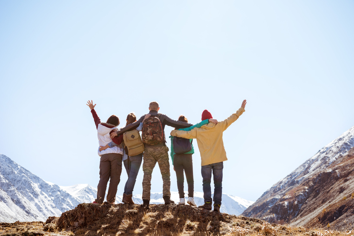 Five happy friends are standing and hugging together in mountains