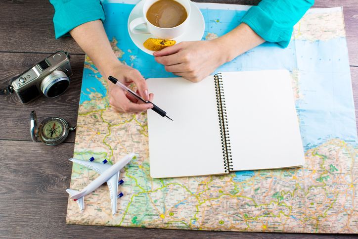 Fascinated by the traveler. Woman is sitting at the table over the map. Empty space in a notebook for blog entries, you can place your text or information. Top view
