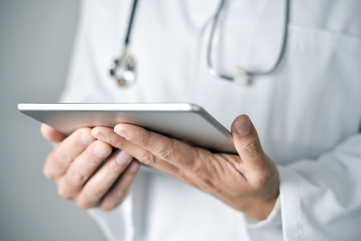 closeup of a young caucasian doctor man wearing a white coat using a tablet computer