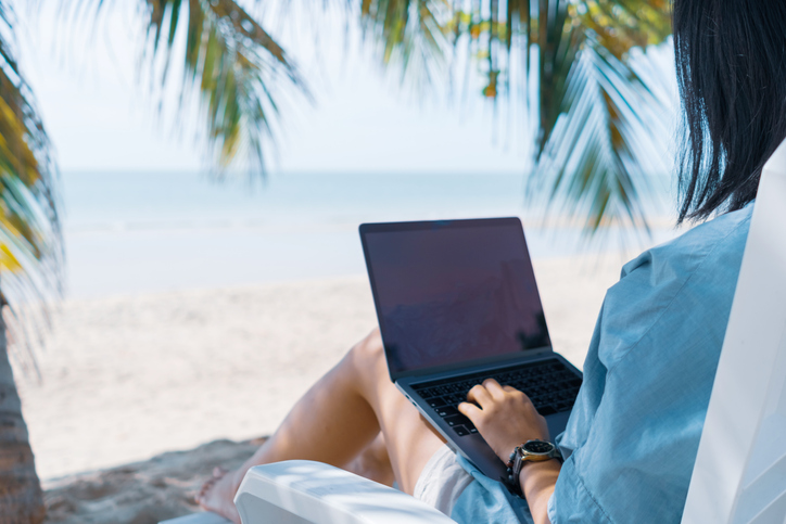 Woman using laptop and smartphone to work study in vacation cady at beach background. Business, financial, trade stock maket and social network concept.