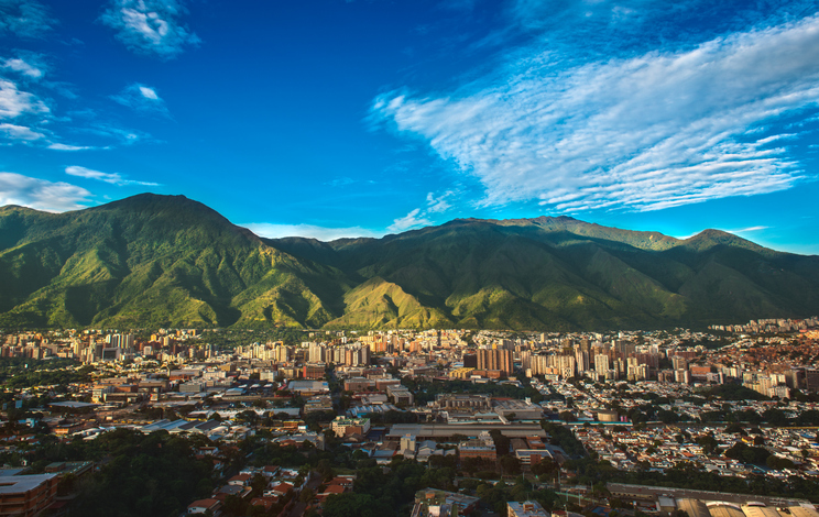 Photograph of Caracas, a Venezuelan city under siege from organized crime and corruption, shot during a beautiful sunny November afternoon displaying the vibrant contrast between the inherent beauty of the city (as shown from a far wide angle shot) and the internal dangers of its daily life.