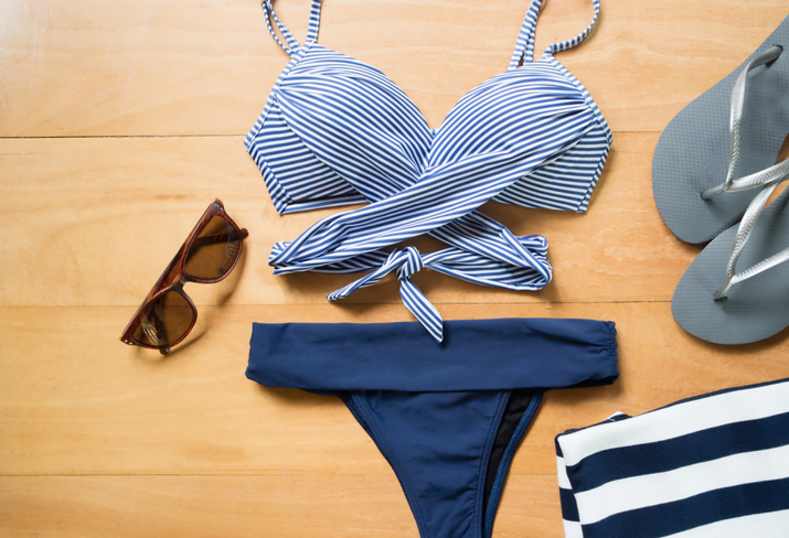 Beach summer clothes and accessories. Bikini. Fashion trends set. Vacation concept. Blue navy and stripes. Top view.